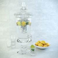 Carafe of lemonade, glasses and a plate with lemons.