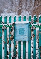 Close up of a mailbox on the street with blue fence